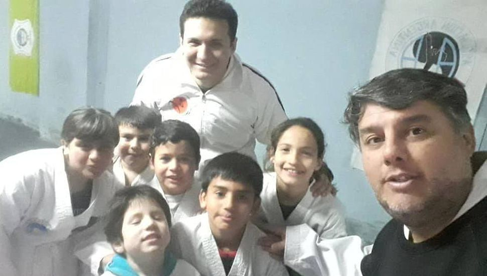 El maestro Gabriel Cova (derecha) posando con el profesor Nicolás Díaz y sus alumnos, en la visita a General Pinto