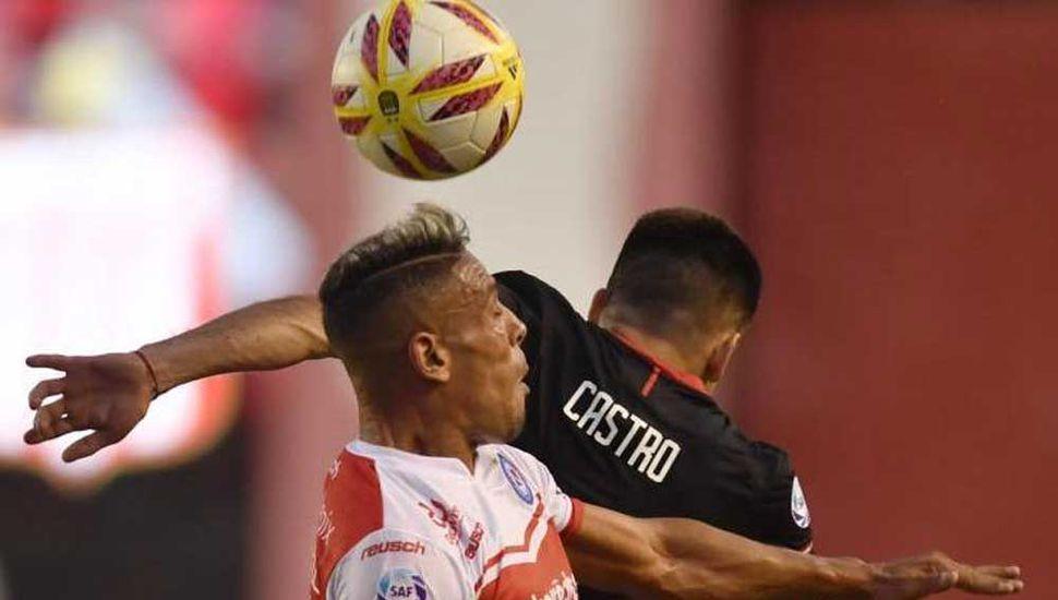 El defensor de Argentinos Juniors rechaza de cabeza ante Manuel Castro (Estudiantes).