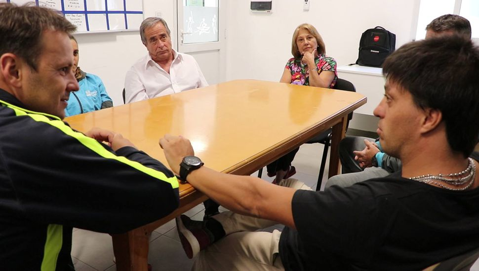 Hernán Saccani dialogando con Daniel Pueyo, ante la atenta mirada de los padres del deportista.