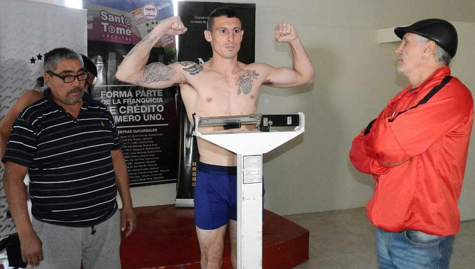 """Pesa Nicolás De León (dio 61 kilos), a quien observan Oscar Farías, presidente de la Comisión Municipal de Box (izquierda) y el técnico Juan Martín """"Látigo"""" Coggi."""