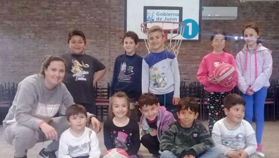 Niños que concurren a la Escuela de Iniciación Deportiva en Fortín Tiburcio, junto a la profesora de básquetbol.