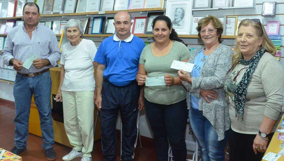 Graciela García, presidenta de la Cooperadora y otros miembros de la entidad, al entregar los premios a los beneficiarios (foto, gentileza de Pablo Bramajo).