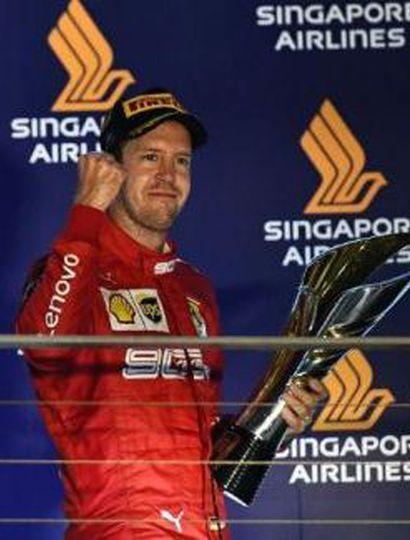 El alemán Sebastian Vettel ganó con la Ferrari y festeja en el podio.