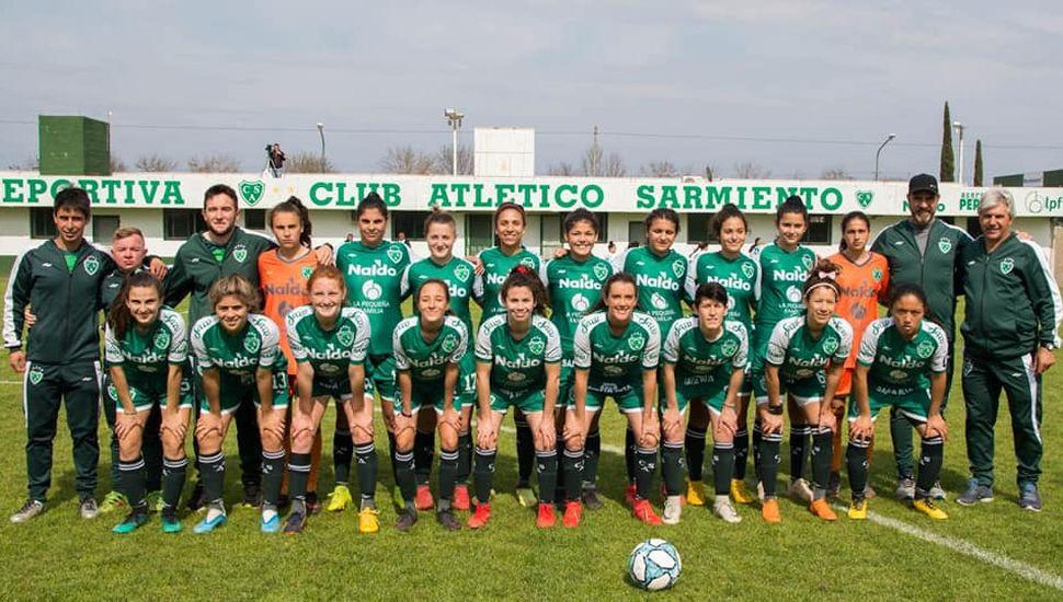 Plantel y cuerpo técnico de primera de fútbol femenino de Sarmiento que debutó goleando y hoy quiere su segundo triunfo.