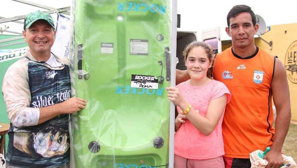 """Gabriel López (izquierda) y José González le entregan el kayak """"Rocker"""" a Clara Beloqui."""