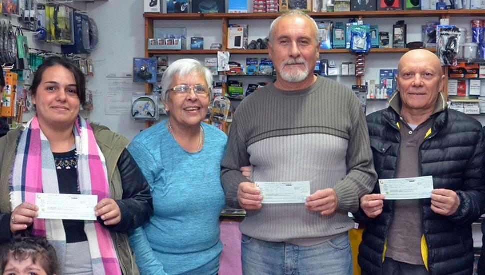 Los premiados al recibir las órdenes de compra obtenidas en un nuevo sorteo de la rifa del Hospital Municipal de  General Pinto (foto, Pablo Bramajo).