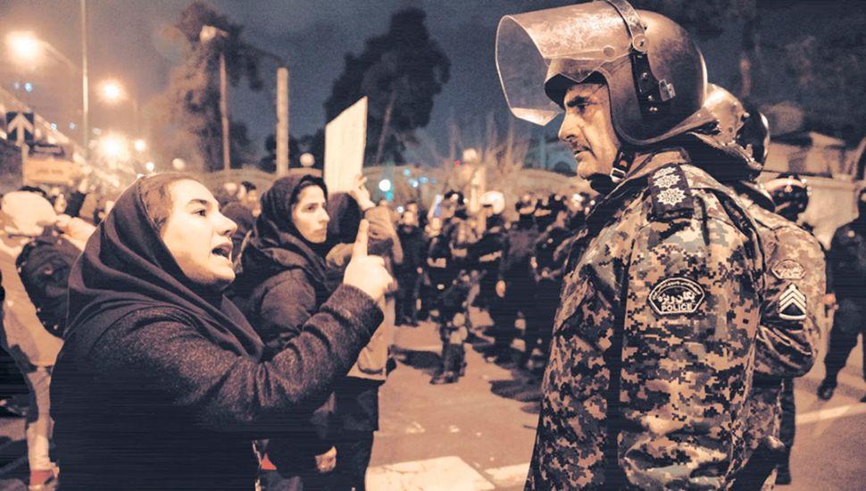 Una mujer increpa a un policía en Teherán durante una vigilia en memoria de las víctimas del avión.