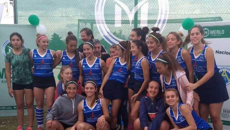 Las jugadoras Sub-16 de la Liga Villeguense de hockey sobre césped festejan con la copa obtenida por el subcampeonato logrado en el nacional disputado en Merlo.
