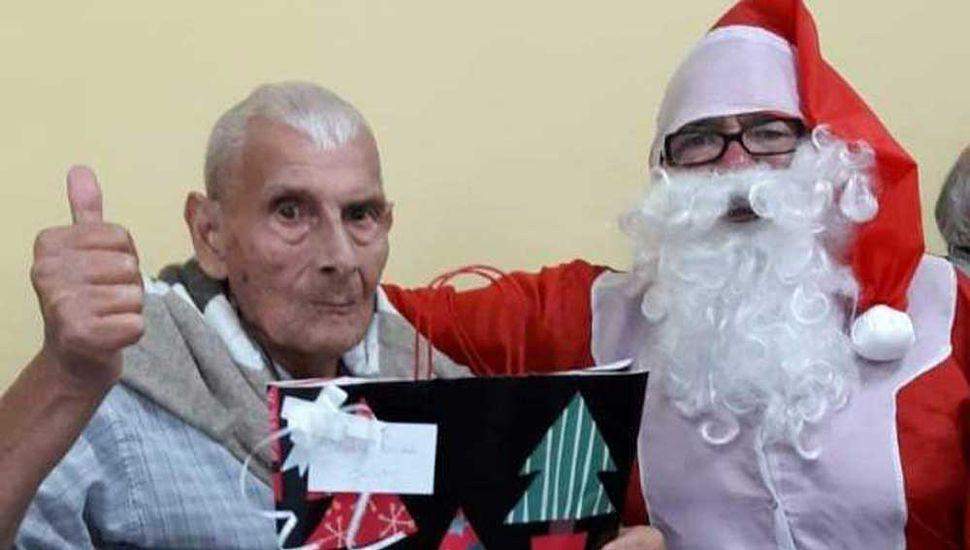 Uno de los abuelos alojados en la Casa, Benito Arias, posando con Papa Noel.