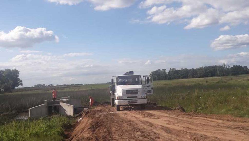 Camiones transportan la tierra y las máquinas compactan el suelo.