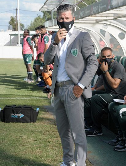 El DT local, Mario Sciacqua,  con traje gris y zapatillas deportivas blancas y grises.