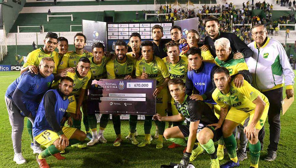 Los jugadores de Defensa y Justicia festejan con el cheque de 670.000 pesos tras vencer a Gimnasia y Tiro de Salta.
