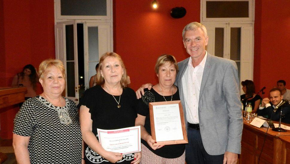 Liliana, María Rosa y Miriam, al recibir el reconocimiento a su padre.