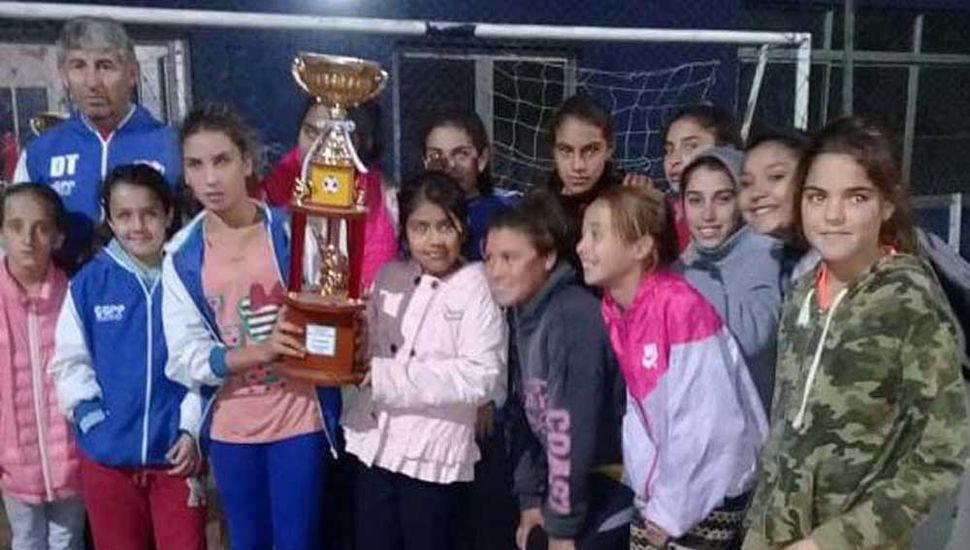 """Plantel de """"Las ositas"""" junto al técnico, Eduardo """"Yiyo"""" López, posando con el trofeo obtenido en Alberdi, al ser subcampeonas."""