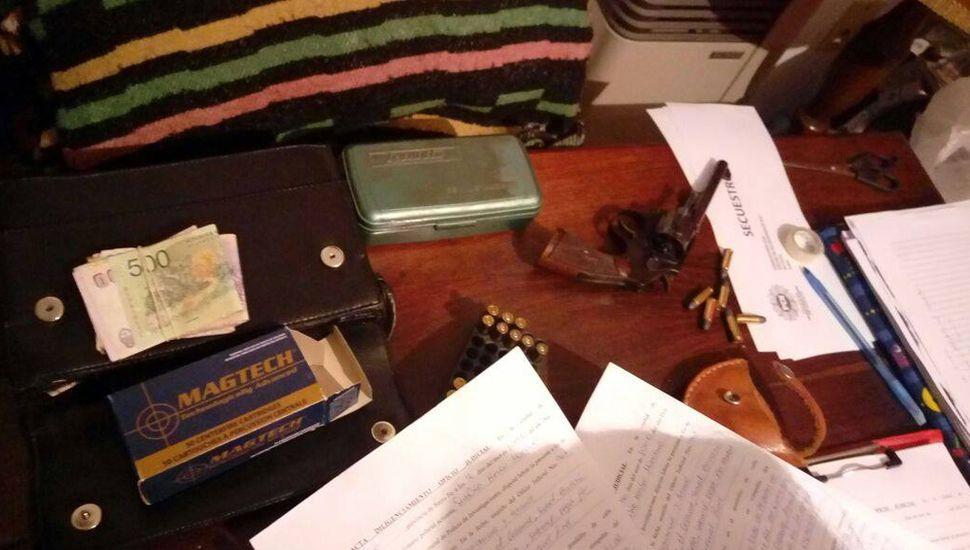 Armas, municiones, dinero, teléfonos celulares y otros elementos confiscados por personal policial.
