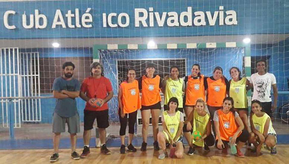 El profesor Gustavo Hernández (pelota en mano) junto a un colaborador y jugadoras.