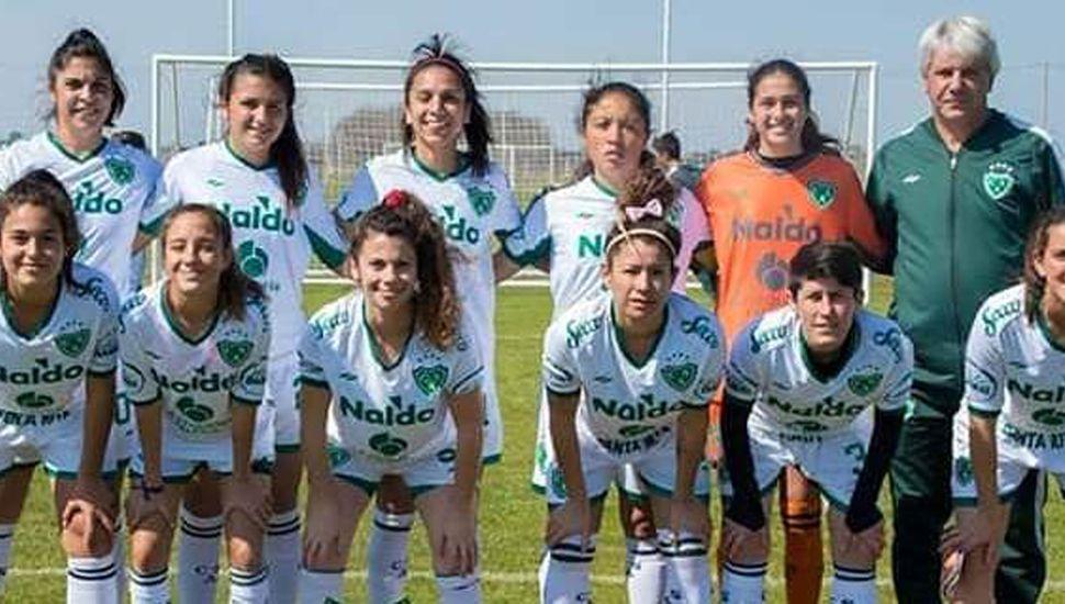 """El técnico Sergio Barbagelata y el equipo de fútbol femenino de Sarmiento de Junín, equipo que va hoy por el tercer triunfo consecutivo en el torneo de la Primera """"B""""."""