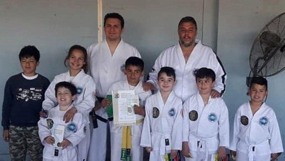 El maestro Gabriel Cova (derecha) y el profesor Nicolás Díaz con alumnos que rindieron exámenes de Taekwon-Do en General Pinto.