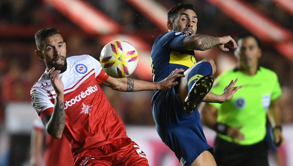 Carlos Tevez (Boca) disputando el balón con Miguel Torren, zaguero de Argentinos Juniors. La primera semifinal terminó en tablas, sin goles.