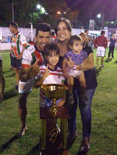 El gran goleador, junto a su familia, con la copa de campeón.