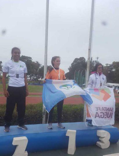Naomi Sampaio  en el podio (izquierda), junto a quienes ganaron la medalla de oro (centro) y la de bronce.