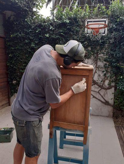 Cangelosi restaurando un mueble de madera.