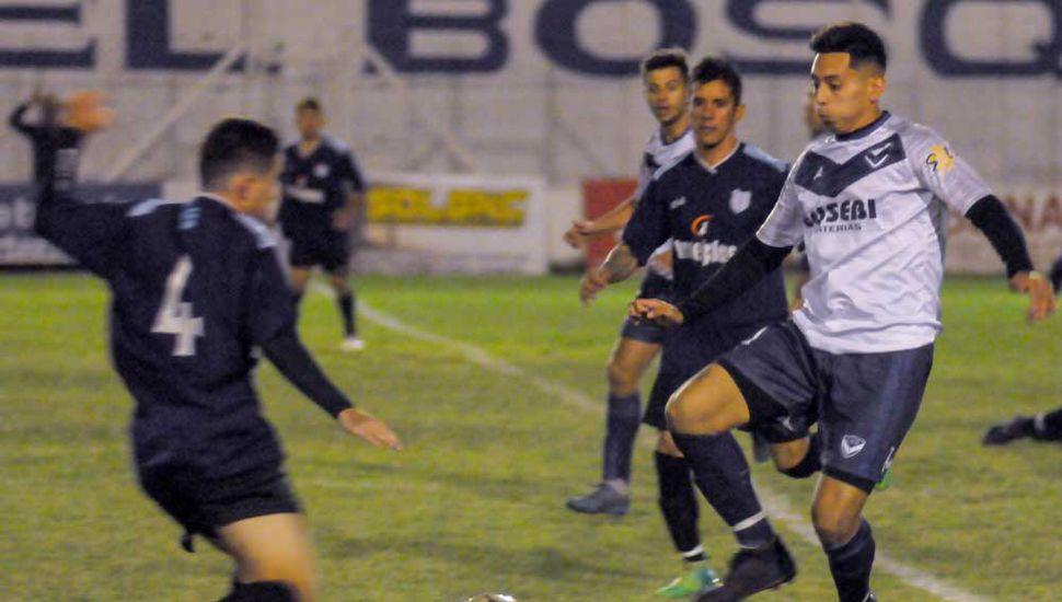Sebastián Yocco (N°4) va a la marca del delantero de Villa Belgrano, en jugada de media cancha.