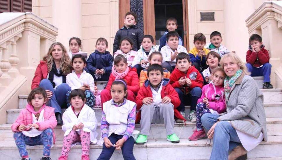 Los educandos y las docentes Malvina Cruz y Carina Librandi sentados en las escalinatas del palacio municipal.