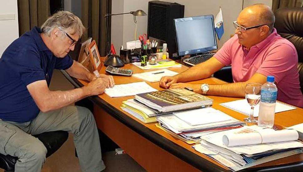 El presidente de la Cooperativa, Luis Gloazzo, al refrender la documentación, junto al intendente Alexis Guerrera.