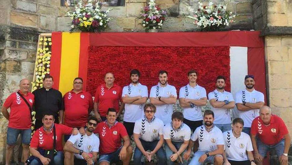 En las patronales de la Virgen del Puerto, el equipo de Santoña, con Fabrizio Casanova (arriba, tercero desde la derecha), posa ante un mural y junto al Párroco local.