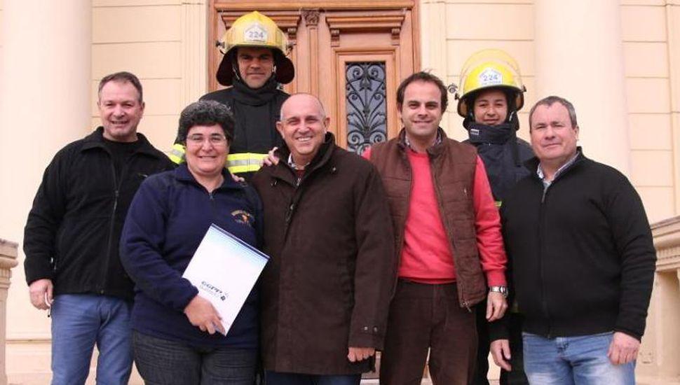 El intendente Alexis Guerrera, Jorge Zavatarelli y Gabriel López posan en las escalinatas del Palacio Municipal con los integrantes de la Asociacióny cuerpo activo de Bomberos Voluntarios de Coronel Granada.