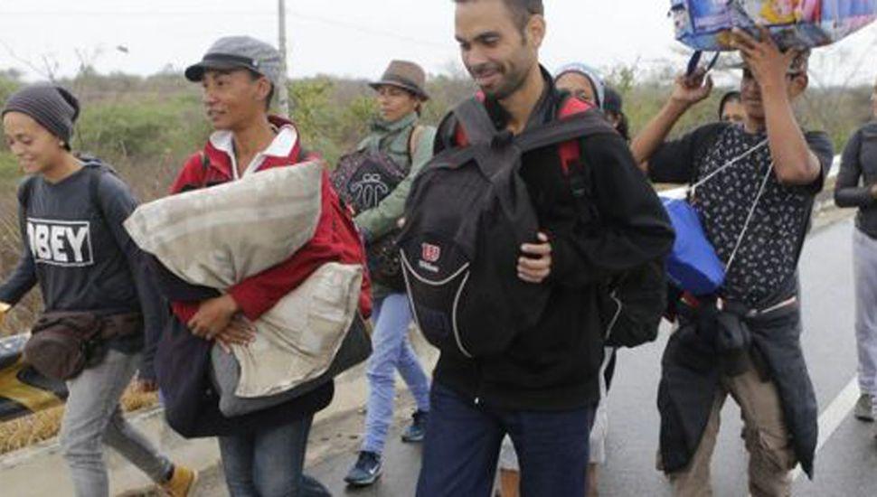 Migrantes venezolanos caminan hacia la frontera con Perú.