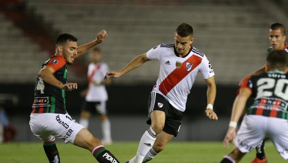 Ignacio Fernández encabeza una carga de River Plate, mientras va a la marca Guillermo Soto, de Palestino.