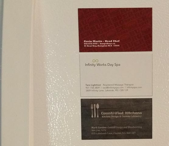 Three business card magnets on a fridge.