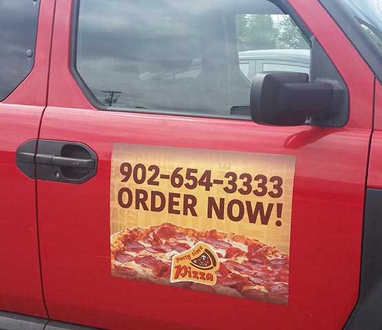 Pizza delivery magnet on a red SUV.