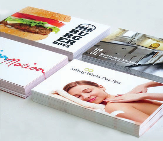 Four stacks of assorted business cards.