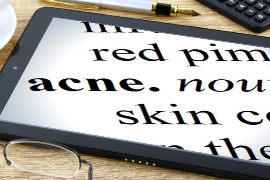 Tablette tactile allumée avec écran blanc et écritures noires (red acne skin) posée sur un bureau en bois clair à côté d'un stylo plume, d'un clavier d'ordinateur et d'une paire de lunette