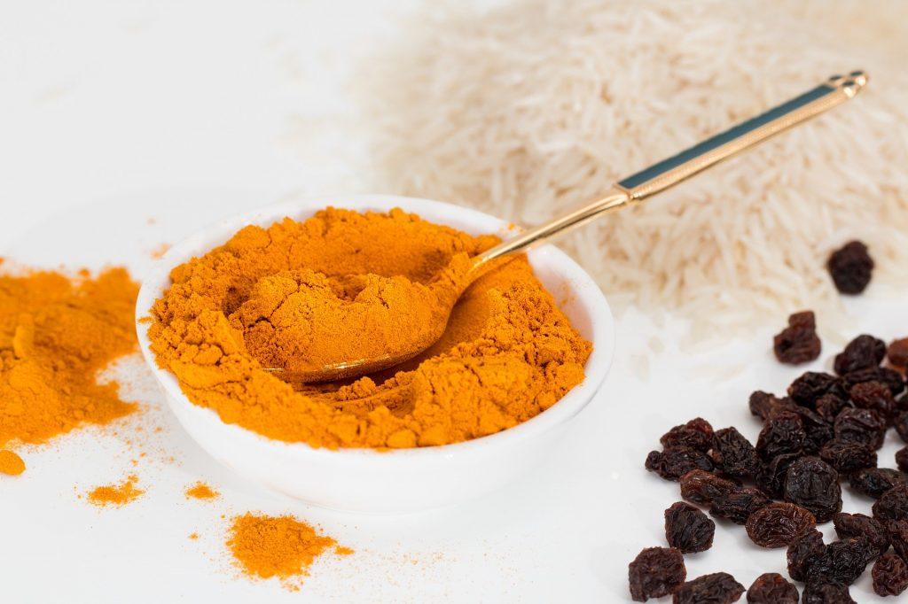 Curcuma en poudre dans un bol : comme épice, il ne présente aucun risque de surdosage.