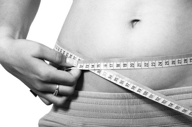 Femme en train de mesurer son tour de taille: la réflexologie plantaire peut favoriser la perte de poids.