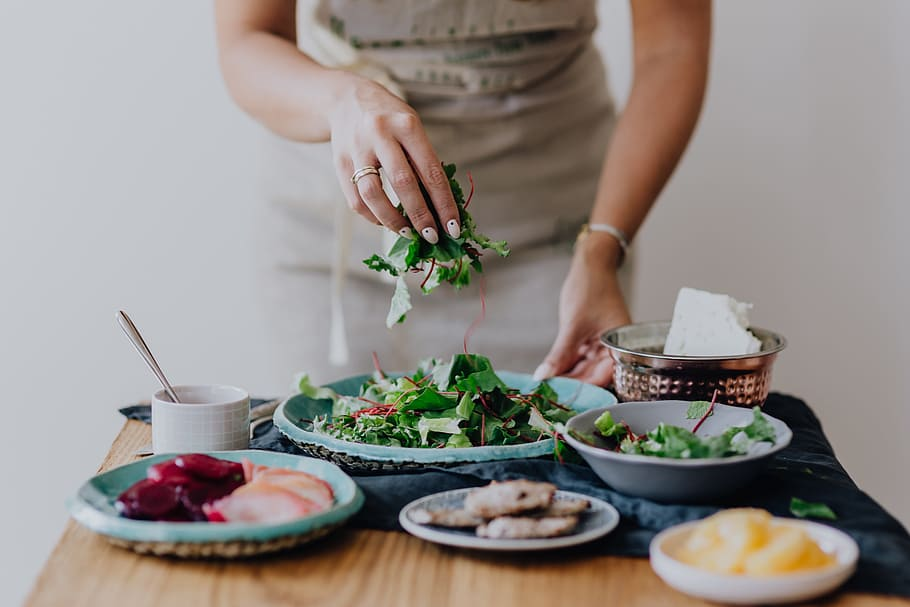 Femme dressant des plats : une alimentation équilibrée booste la fertilité féminine.