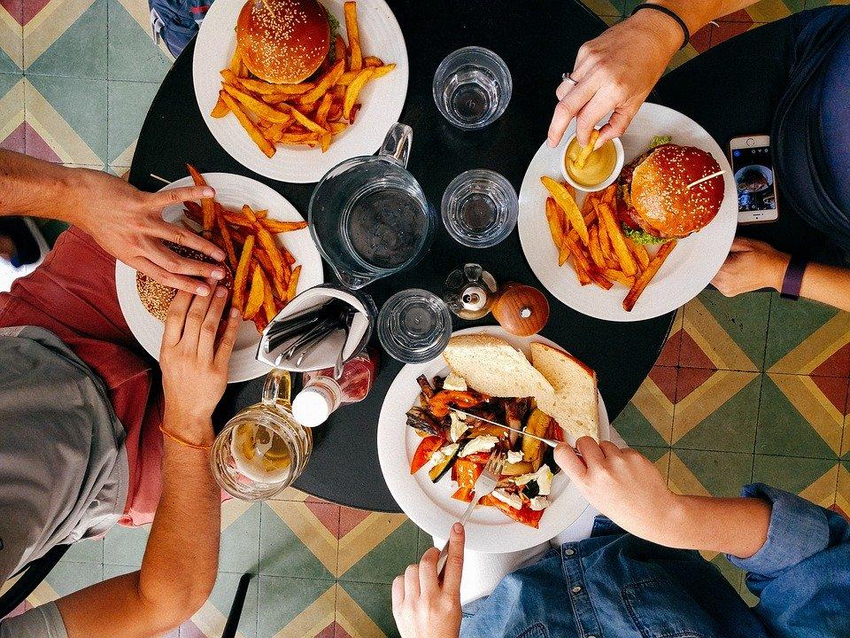 Hommes vus d'en haut, assis à table : l'alimentation peut avoir un impact direct sur la fertilité masculine.