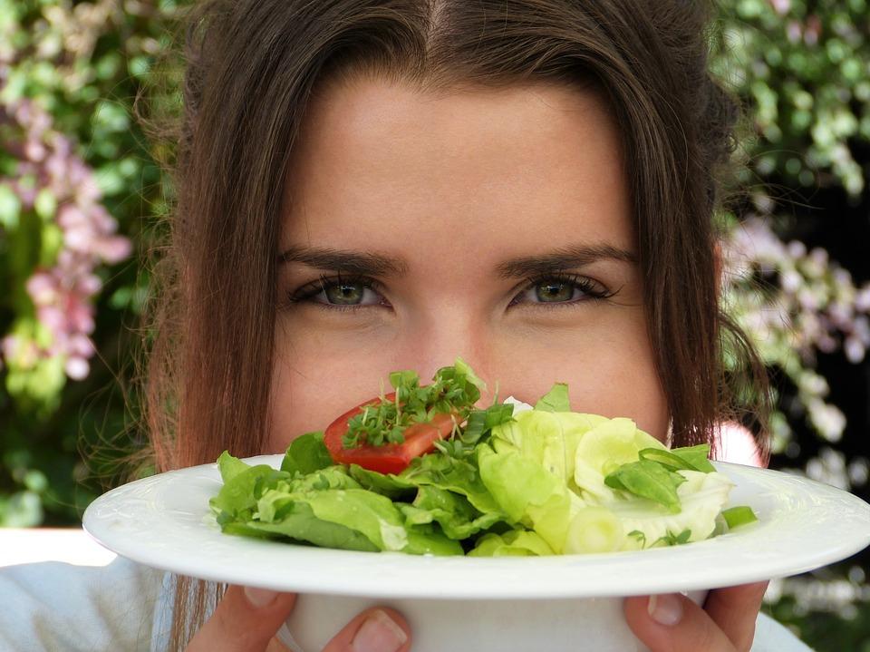 Femme au regard fixe tenant une assiette: santé des yeux et alimentation.