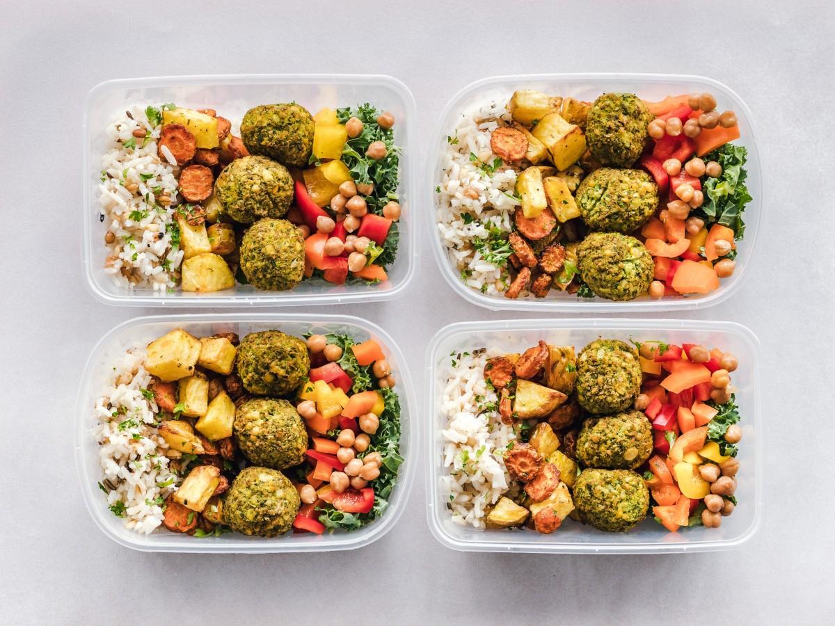 Bols contenant du riz, des falafels et des légumes: aliments conseillés dans le cadre d'un régime végétalien pour sportif.
