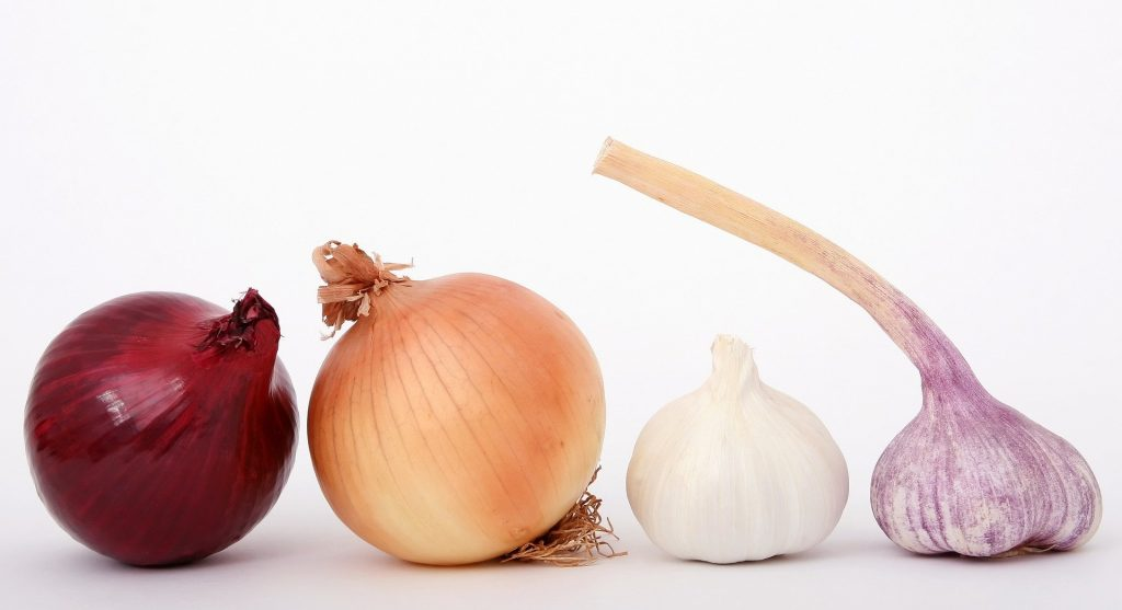 Aliments riches en soufre: les alliacées, oignons et ail.