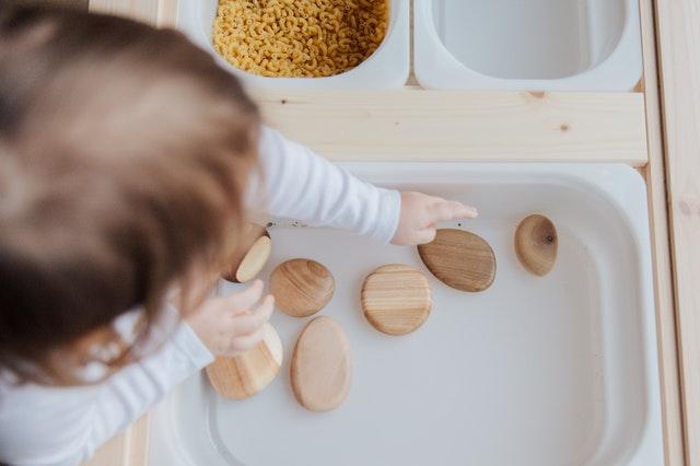 Enfant en train de mettre en œuvre la pédagogie Montessori: définition, méthode et grands principes.