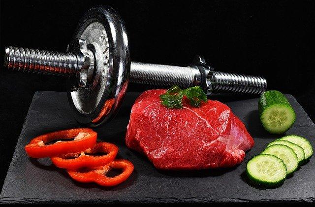 Viande rouge et haltère de musculation sur un plateau: aliment recommandé pour le régime sèche et la prise de masse musculaire.