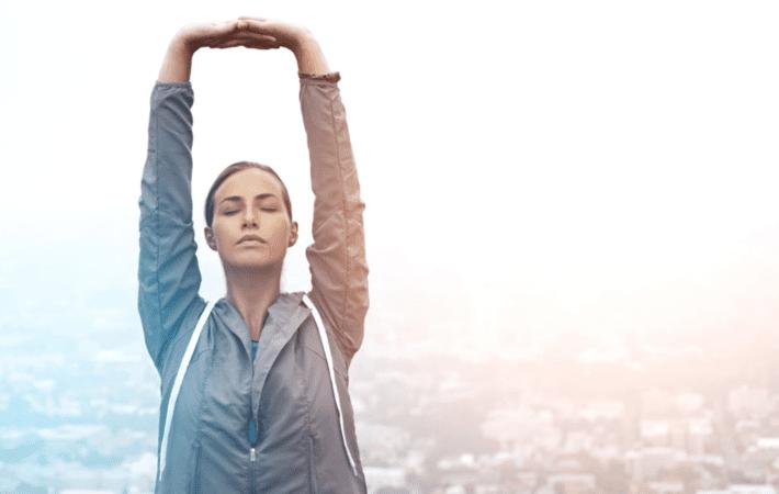 Posture du yoga: étirement des bras vers le ciel, pour soulager le mal de dos.