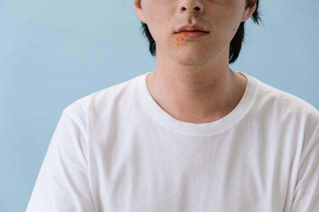 Homme souffrant d'herpès labial : causes et traitement naturel.