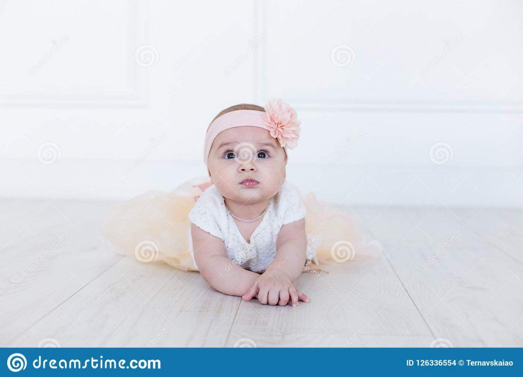 Image représentant un bébé réalisant une posture de yoga, la posture du sphinx.