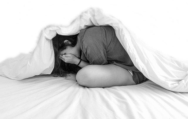 Femme dans un lit, souffrant d'anxiété nocturne.
